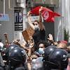 Une manifestante portant le drapeau tunisien est soulevée dans la foule.