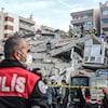 Un policier turc regarde un immeuble effondré.