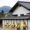 Les quatre hommes marchent les uns derrière les autres, de l'eau jusqu'à la taille.