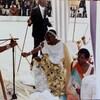 Un homme en costume traditionnel reçoit un sceptre lors d'une cérémonie en Afrique.