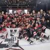 Tous les membres de l'équipe néo-brunswickoise rassemblés sur la patinoire font des signes de victoire.