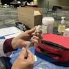 Une femme se prépare à administrer un vaccin.