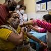 Une femme est crispée en recevant sa dose de vaccin, qu'une travailleuse de la santé lui administre.