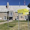 Le Manoir du Saguenay de l'extérieur et une affiche de clinique de vaccination contre la COVID-19.