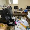 Un bureau saccagé avec des classeurs ouverts et des documents sur le sol.