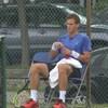 Il est assis sur une chaise au bord d'un terrain de tennis.