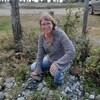 Le femme pose près d'une petite forêt. Elle sourit et porte des lunettes.