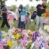 Une mère et ses deux filles sont devant le monument de fleurs commémorant les victimes.