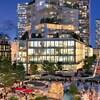 Il s'agit d'une image modélisée du futur village urbain. Des tours d'habitations illuminées sont construites de part et d'autre d'un boulevard. Au premier plan se trouve une place avec une fontaine, des tables, des chaises et des parasols.