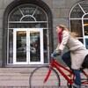 Une dame sur un vélo devant un édifice.