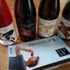 Quatre bouteilles de vin posées derrière un guide de vin.