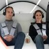 Deux personnes attachées à bord d'une cabine ronde de couleur blanche.
