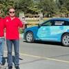 Deux hommes posent devant une voiture électrique.