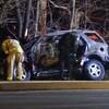 Des pompiers et des policiers inspectent la carcasse incendiée d'une voiture.
