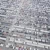 On voit du haut des airs des centaines de voitures neuves alignées dans un stationnement.