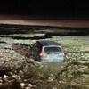 Un véhicule à moitié submergé dans l'eau glacée en pleine nuit.