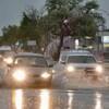 Des voitures roulent sur une rue où une bonne quantité d'eau s'est accumulée.