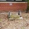 Un socle en béton avec deux anses en métal posé sur le sol