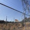 Un panneau indiquant un haut voltage se trouve sur la clôture qui protège un pylône électrique.