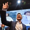 Un homme souriant et portant un complet devant des écrans géants fait un signe de la main.