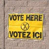 Une affiche jaune d'Élections Nouveau-Brunswick qui indique « Votez ici ».