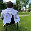 Un homme assis devant une maison. Des avertissements de risque pour la sécurité de la communauté, avec une grande photo de Wade Stene, sont collés sur le dossier de sa chaise.