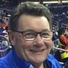 Warren Woods, assis dans les gradins, sourit lors d'un événement sportif.