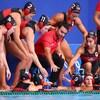 Les joueuses sont rassemblées sur le bord de la piscine avec leur entraîneur.