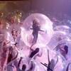 Un homme encapsulé dans une bulle de plastique géante chante devant une foule dont les fans sont également dans une bulle.