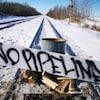 Plan serré d'un barrage sur un chemin de fer où une affiche indique en anglais : « pas de pipeline ».