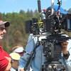 Simon Marcotte et à côté du caméraman. La grosse caméra de cinéma est montée sur un trépied.