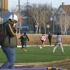 Une dizaine de jeunes jouent au soccer, alors qu'un homme portant un masque passe devant le terrain.
