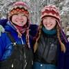 Deux jeunes filles qui se ressemblent sourient à la caméra. Elles sont dehors dans la neige. Celle de droite a le bras droit passé sur les épaules de celle de gauche.