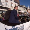 Yves-François Blanchet assis à l'arrière d'une voiture décapotable que des passants regardent défiler.