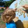 Un enfant regarde la planète terre avec un adulte à ses côtés.