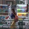 Une femme marche dans la rue au Japon devant des machines distributrices.