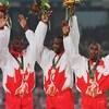 Quatre coureurs canadiens célèbrent leur médaille d'or sur le podium.