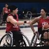 Deux joueuses de basketball en fauteuil roulant discutent de stratégie.