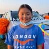 Kaitlyn Chen devant un véhicule décoré avec des anneaux olympiques et un drapeau du Canada.