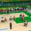Un joueur de basketball en fauteuil roulant tente un tir sous les yeux des autres joueurs.