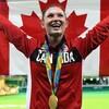 La trampoliniste, Rosie MacLennan, souriant avec le drapeau canadien et sa médaille d'or au cou.