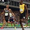 Le sprinteur canadien Andre De Grasse souriant à Usain Bolt en pleine course aux Jeux de Rio en 2016.