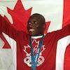 Un lutteur canadien soulève le drapeau du Canada avec sa médaille d'or olympique au cou.