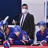Il regarde l'action derrière le banc du Canadien de Montréal, où se trouvent quatre joueurs.