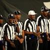 Sept arbitres sont côte à côte et posent pour les photographes avant un match de football.