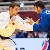 Il porte un judogi blanc et agrippe un adversaire