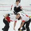 Trois hommes pratiquent le curling