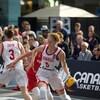 Une joueuse de basketball protège son ballon pendant un match devant les yeux de spectateurs attentifs.