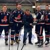 Joueurs de hockey côte-à-côtes, tenant un trophée.