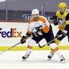 Le joueur de centre des Flyers contrôle le disque, surveillé par un défenseur des Penguins.